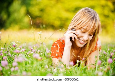 Young beautiful smiling woman lies on lawn and talks by mobile phone.
