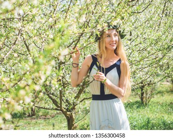 Young beautiful smiling woman with long blond hair in bay leaf wreath in spring blossom cherry garden.