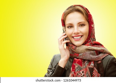 Young beautiful smiling woman in motley red headscarf talks on cellular telephone isolated on yellow background.