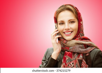 Young beautiful smiling woman in motley red headscarf talks on cellular telephone isolated on red background.