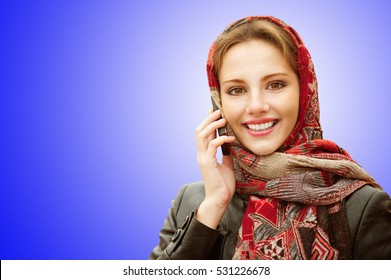 Young beautiful smiling woman in motley red headscarf talks on cellular telephone on blue background.
