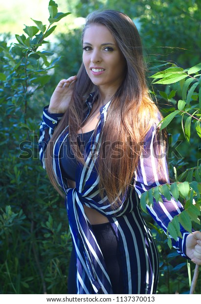 young beautiful smiling woman in nature forest sun light