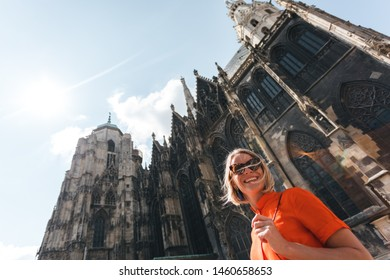 Young beautiful smiling woman in orange dress on the background of St. Stephen's Cathedral in Vienna, Austria