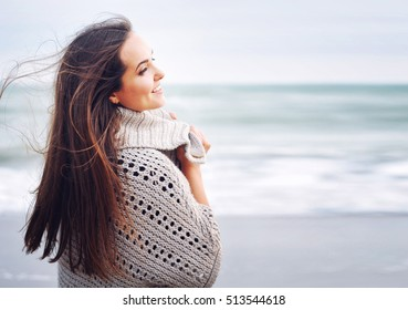 Young beautiful smiling woman portrait against ocean background, winter outdoor