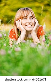 Young beautiful smiling woman in red dress lies on green summer meadow.
