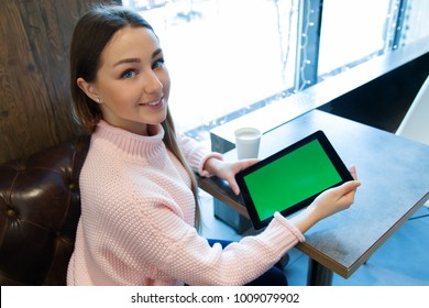 Young beautiful smiling woman is  sitting on the table in cafe and demonstrating, showing the screen of her  tablet