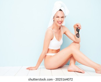 Young beautiful smiling woman in white lingerie.Sexy carefree model in underwear and towel on head posing near light blue wall in studio. Positive and happy female enjoying morning.Sitting and winking