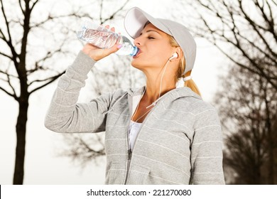 Young beautiful sport woman drinking water after running in nature.
