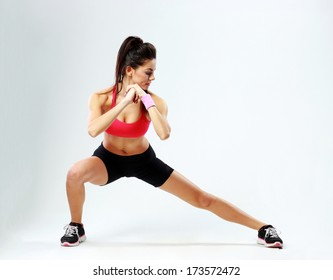 Young beautiful sport woman stretching legs on gray background