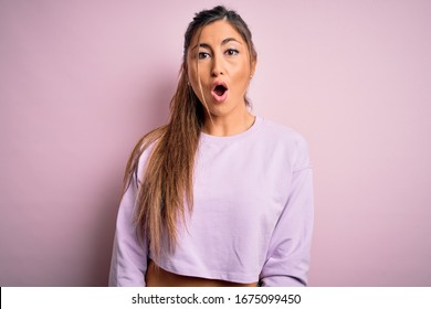 Young beautiful sport woman wearing sweatshirt over pink isolated background afraid and shocked with surprise expression, fear and excited face.