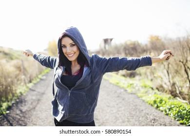 Young beautiful sportive woman raising arms.