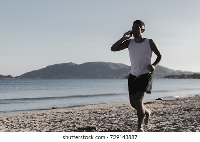 Young beautiful sports black man running near sandy beach while speaking on the mobile phone. Healthy lifestyle and communication concept.