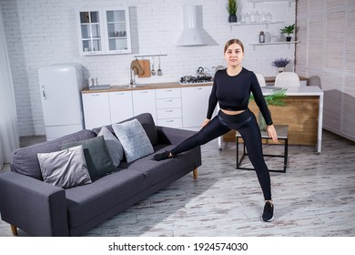 Young beautiful sports girl in leggings and a top does exercises at home on the couch. Healthy lifestyle. The woman goes in for sports at home.