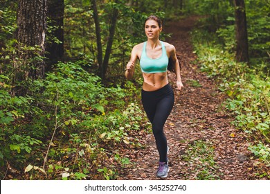 Young beautiful sporty girl in short green sports top training in green forest during summer autumn season with lots of fallen leaves on path. Front view with copy space full length portrait of runner