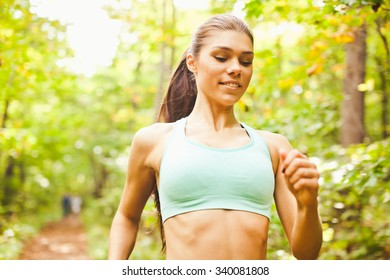 Young beautiful sporty inspired girl in short green sports top training in green forest during summer season. Brightly lit scene. Looking down at path