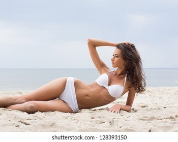 Young, beautiful, sporty and sexy woman relaxing on the beach