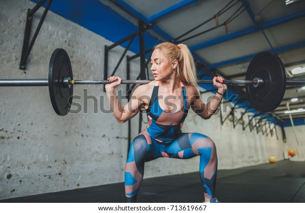 young beautiful sporty woman exercising with barbell in gym