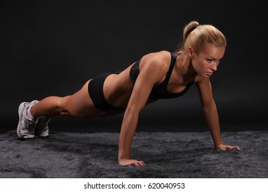 Young beautiful sporty woman on black background. Fit sportswoman stretching
