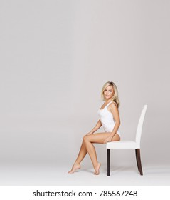 Young, beautiful and sporty woman in slimming underwear. Woman in white lingerie over grey background.