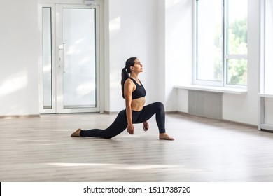 Young beautiful sporty woman wearing black sportswear practicing sport exercises, doing lunges near window in gym, stretching legs and standing on ashtanga pose, Indoor, sports lifestyle
