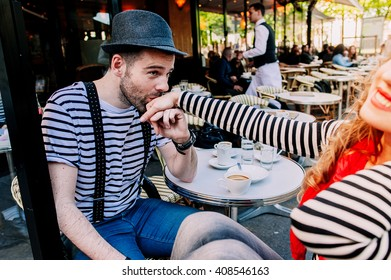 Young beautiful stereotypical french couple kissing and having fun in a Parisian street cafe