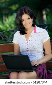 Young beautiful student girl with laptop in the park