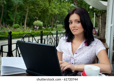 Young beautiful student girl with laptop and cup of coffee in cafe