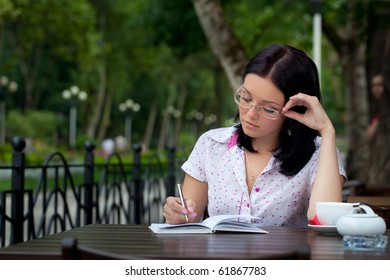 Young beautiful student girl with notepad in the cafe