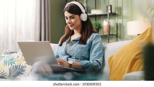 Young beautiful student girl sitting at home on couch typing on laptop enjoying music in white headphones.