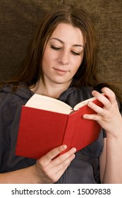 Young beautiful student read book on couch.