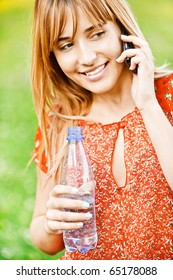 Young beautiful student in red clothes speaks on cellular telephone and has control over bottle with water, on green summer background.