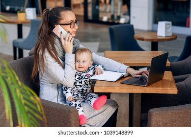Young beautiful stylish businesswoman talking on mobile phone and looking at laptop while sitting with her baby girl at her working place. Freelancer working with baby.