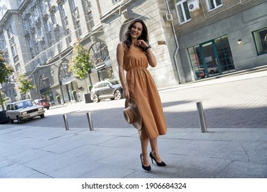 Young beautiful and stylish caucasian woman wearing long romantic dress and high heel shoes looking at camera and smiling while standing on the city street