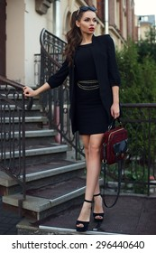 Young beautiful stylish classy girl wearing black dress and coat, holding red handbag, standing and posing at stairway.