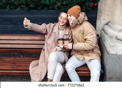 Young beautiful and stylish couple in love have fun together in winter and making funny selfie with smartphone outdoor