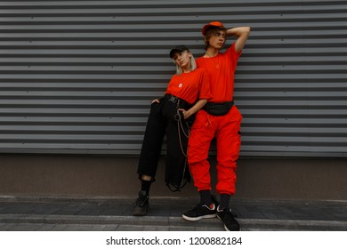 Young beautiful stylish couple models in fashion caps and trendy orange clothes are standing near the gray wall