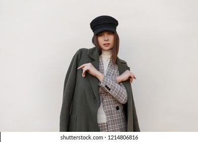 Young beautiful stylish elegant woman in hat with stylish coat and suit poses on the street