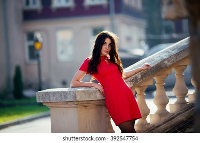 The young beautiful stylish girl with long dark hair, standing outdoors in a red dress at the event. Close up portrait of a beautiful sunset light