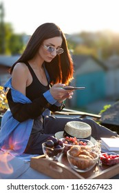 young beautiful stylish girl make photo of herself and food, picnic healthy food and lifestyle concept, mobile photography of  fruits outdoors