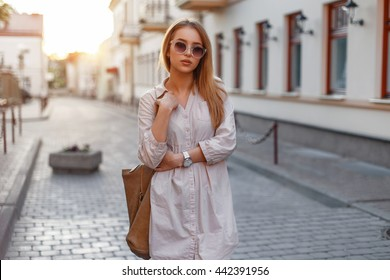 Young beautiful stylish girl in sunglasses on a summer day at sunset.