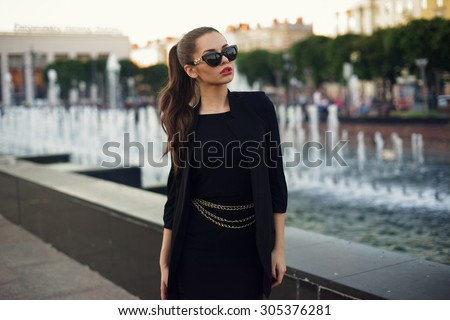 45a49ae5613 Young beautiful stylish girl walking and posing in short black dress in  city near fountains.