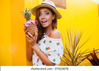 young beautiful stylish hipster woman in straw hat holding pineapple in pink sunglasses, smiling funny, happy summer, yellow wall background, denim shorts, cool t-shirt, trendy outfit, tropic