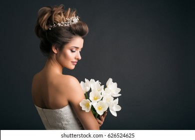 young beautiful stylish woman, bride, bridal fashion, spring trend, flowers, tulips, hairstyle, beauty make-up, white dress, tenderness, innocence, dark background