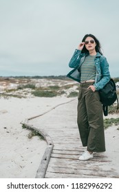 young beautiful and stylish woman holdign her sunglasses and walking in a beach walking trail.