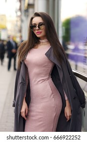 Young beautiful stylish woman with long straight brunette hair walking at the street. Pretty girl in pink elegant dress and coat
