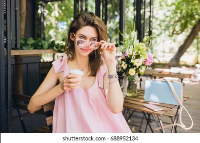 young beautiful stylish woman in pink dress, summer style, sitting in cafe, drinking coffee in paper cup, smiling, happy, positive, having fun