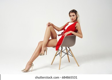 Young beautiful stylish woman posing in white short dress and red jacket on bright gray background. Studio fashion style full length portrait of girl sitting on chair