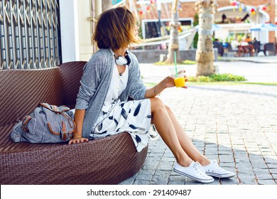 Young beautiful stylish woman, sitting on the street bench, traveling alone, enjoy her free time, wearing vintage hipster trendy outfit, drinking smoothie, enjoy weekends.