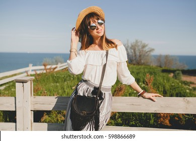 young beautiful stylish woman, spring summer fashion trend, boho style, straw hat, countryside weekend, sunny, smiling, fun, sunglasses, black purse
