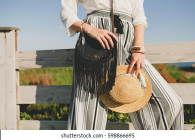 young beautiful stylish woman, spring summer fashion trend, boho style, straw hat, countryside weekend, sunny, smiling, fun, sunglasses, black purse, striped trousers, details, accessories